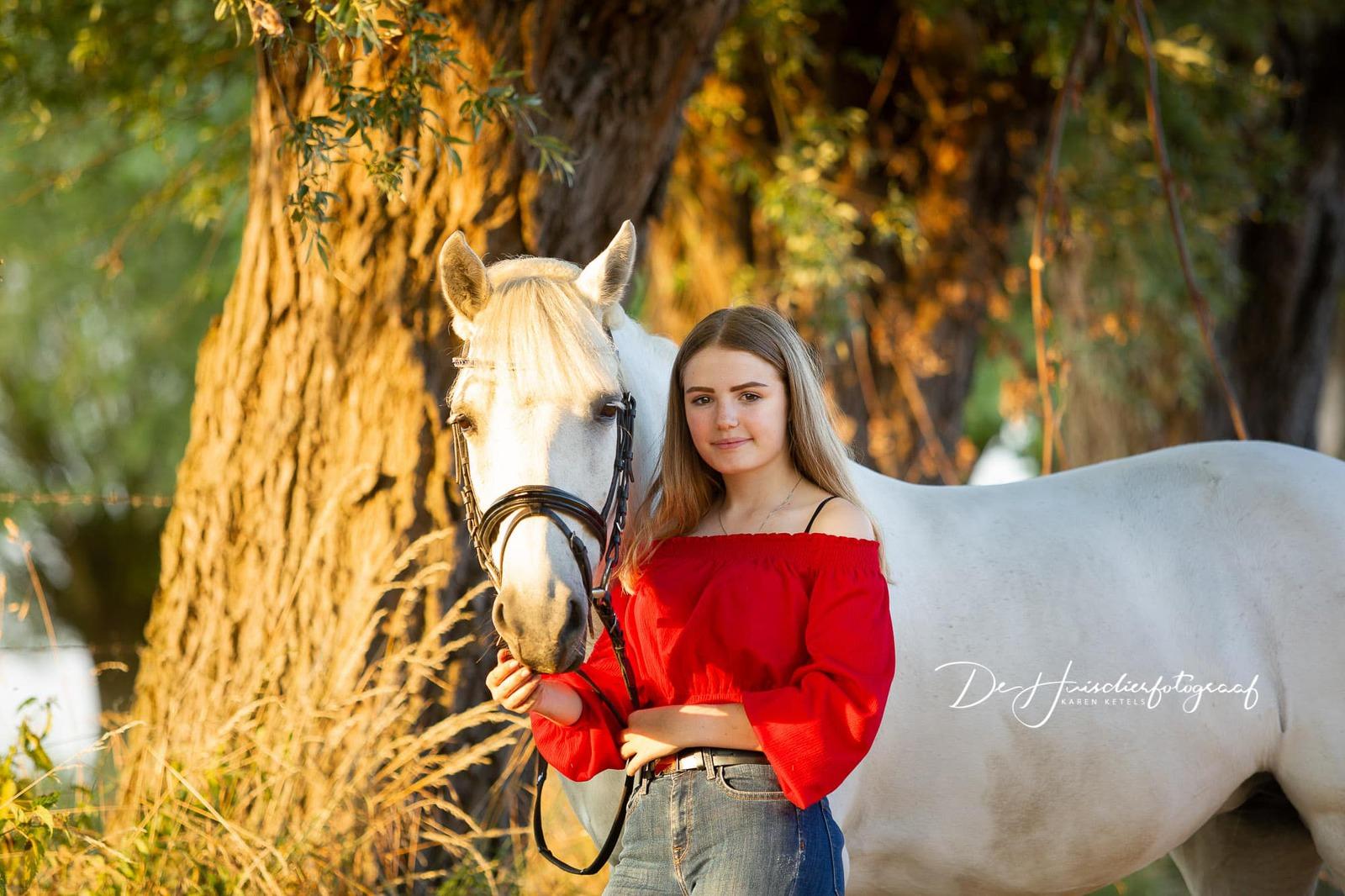 Zomers portret van een meisje met haar witte pony onder de bomen. portret door De Huisdierfotograaf Karen Ketels