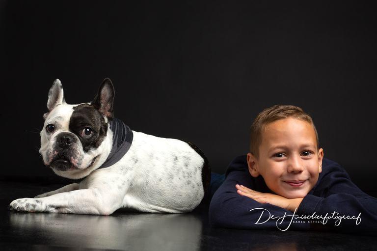 Beste vriendjes; Franse Bulldog ligt zij aan zij met zijn baasje. Zowel het jongetje als de hond kijken recht in de lens van huisdierfotograaf Karen Ketels
