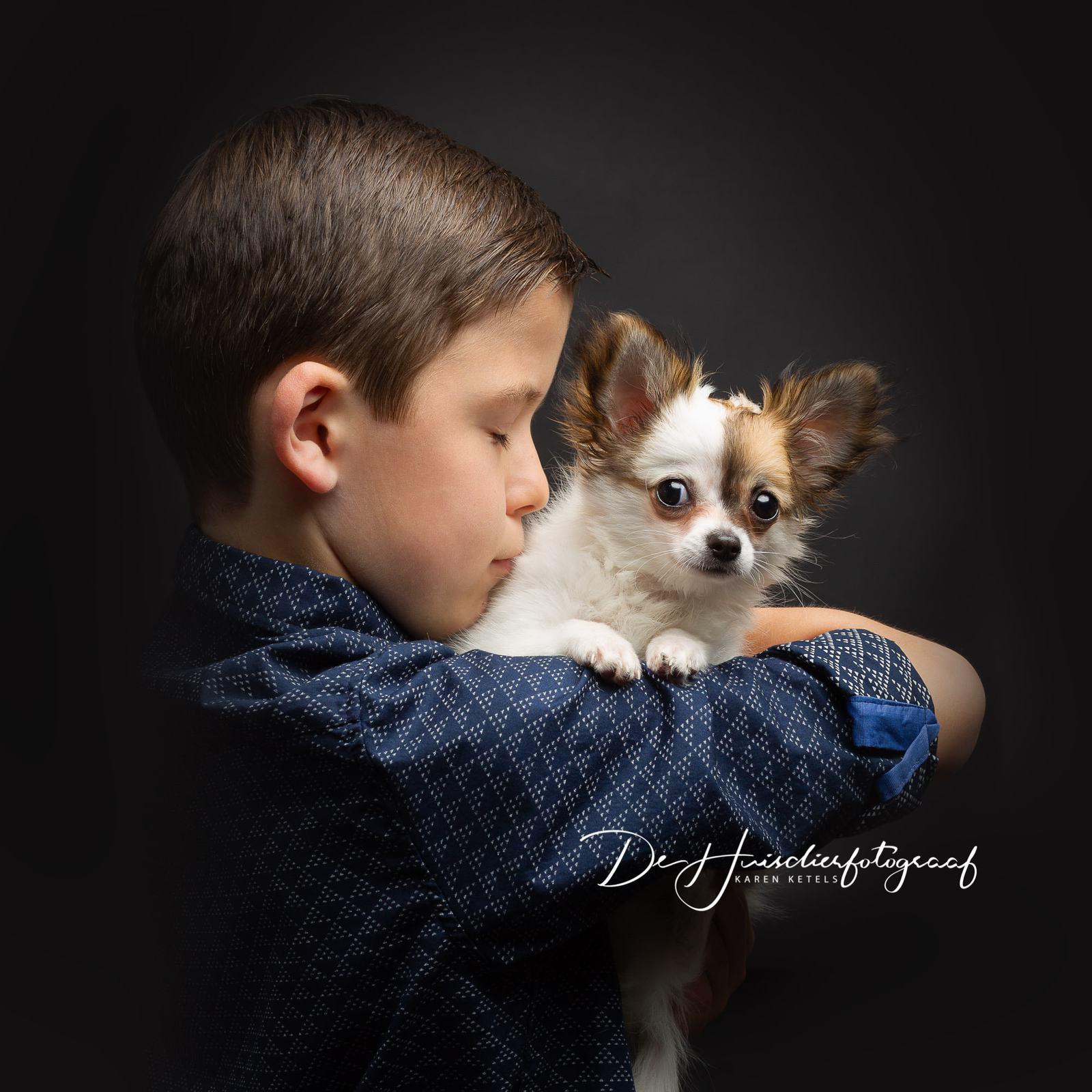 Portret van een jongetje dat zijn chihuahuapup een zoentje geeft. Portret door De Huisdierfotograaf
