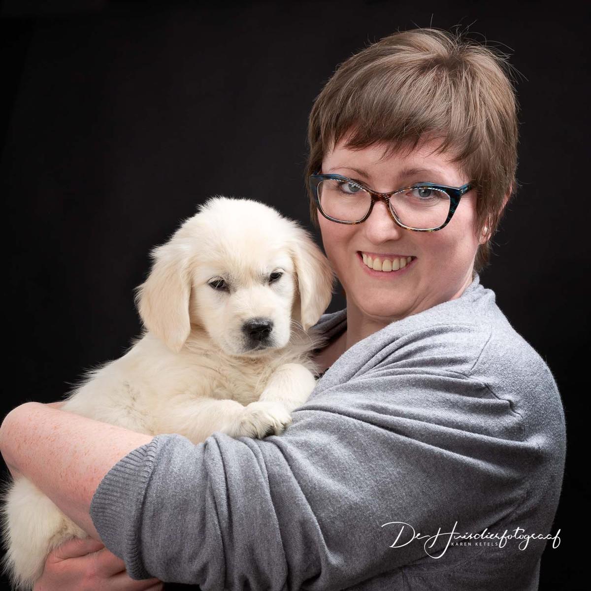 Portret van De Huisdierfotograaf Karen Ketels met op haar arm haar golden retriever puppy Hebe