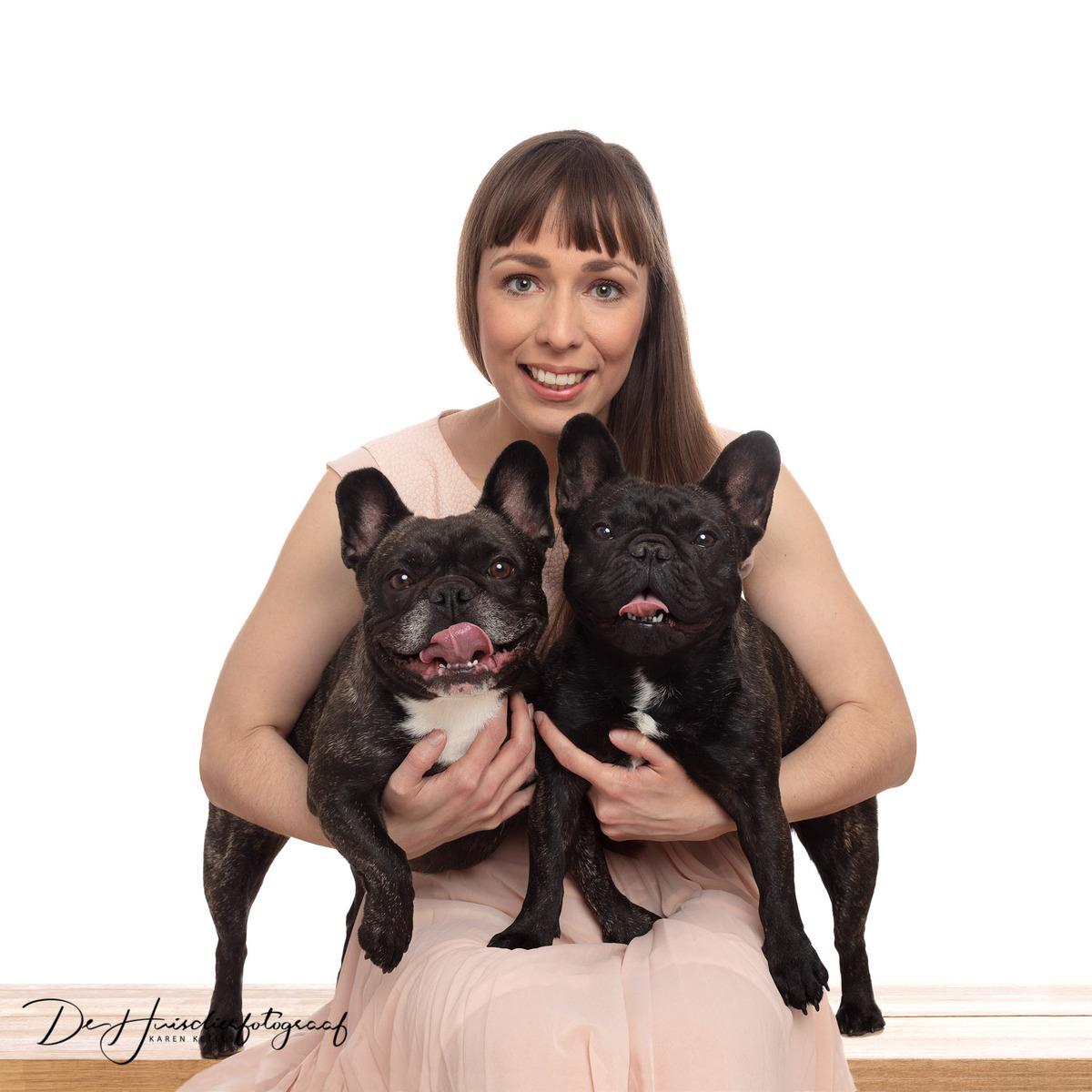 Huisdieren met hun baasjes. Portret van een jonge dame met haar 2 franse bulldogs op schoot. Portret door De Huisdierfotograaf