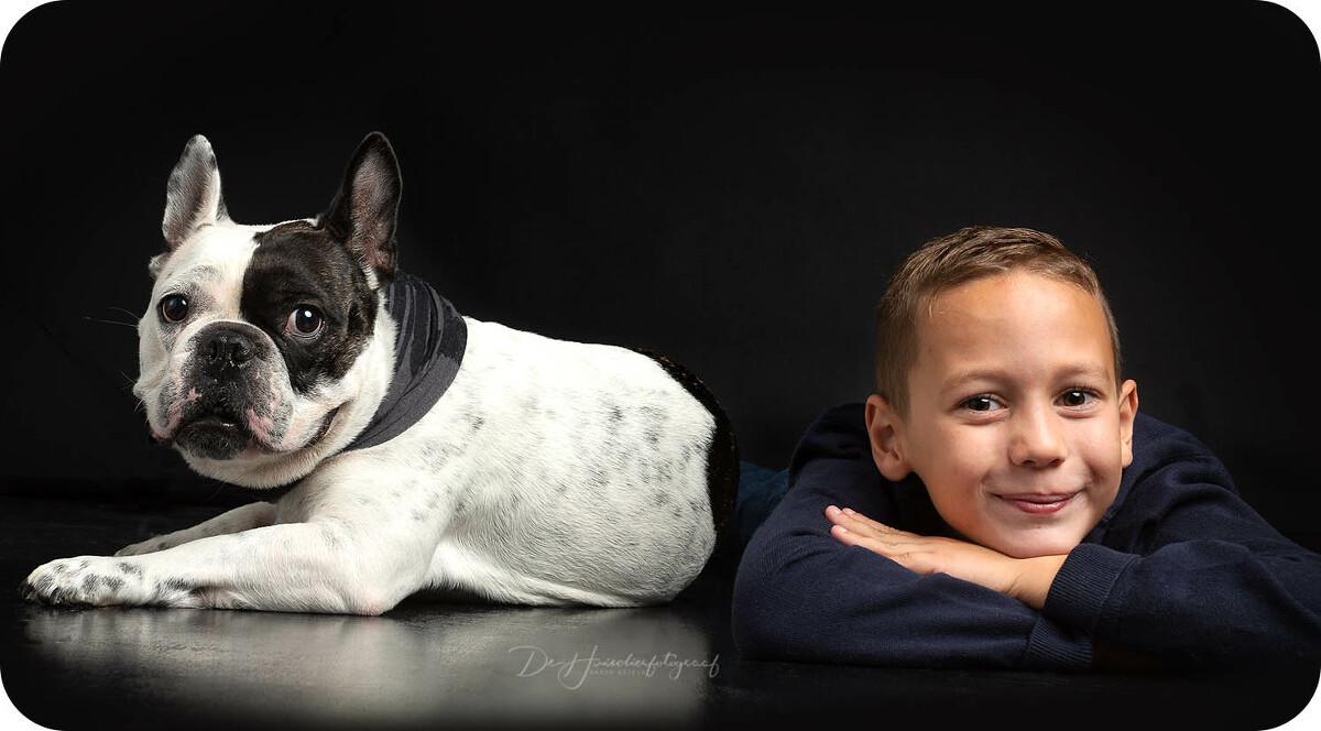 Huisdieren met hun baasjes; Beste vriendjes; Franse Bulldog ligt zij aan zij met zijn baasje. Zowel het jongetje als de hond kijken recht in de lens van huisdierfotograaf Karen Ketels