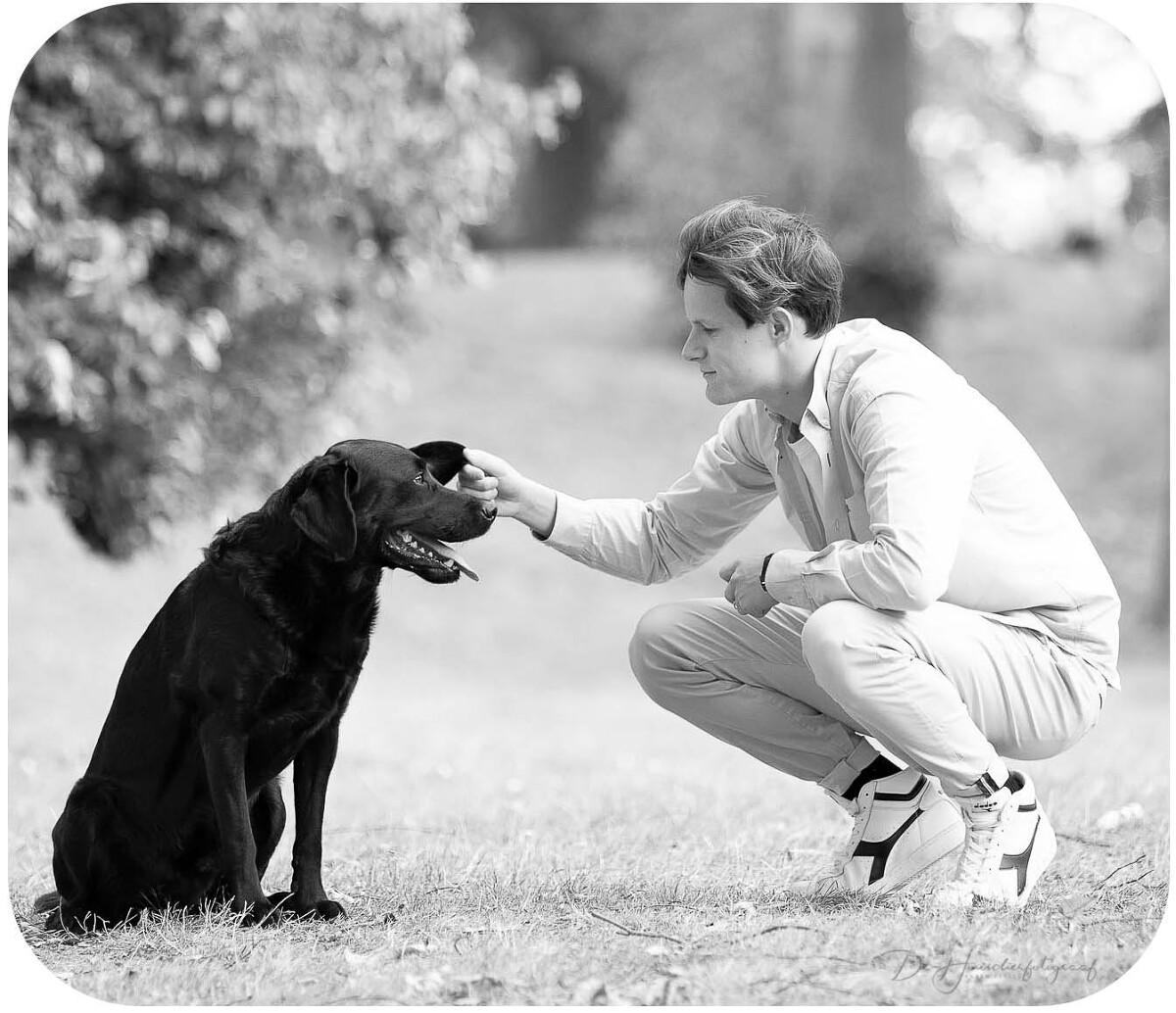 Portret van een zwarte labrador die in volle adoratie naar zijn baasje kijkt. Zwart-wit-portret door De Huisdierfotograaf